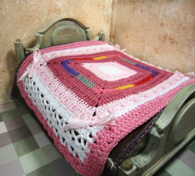miniature dollhouse bedspread crocheted in shades of pink