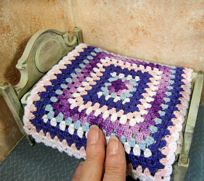 Miniature crochet bedspread worked granny square style.
