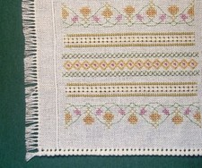 closeup of hem-stitching and needlework stitches on miniature embroidered bedspread