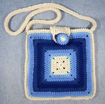 Granny square style purse worked in shades of blue.