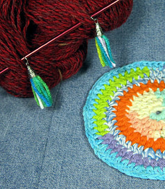 detail of tassel stitch markers and crochet coaster
